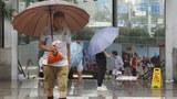中國南方連續降雨,圖爲上海居民在雨中出行。(美聯社)