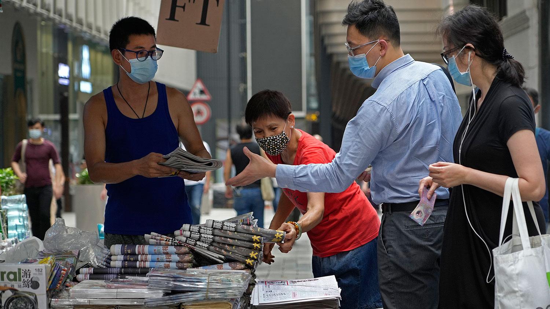 2021 年 6 月 18 日,人們在香港市中心的街道上購買 《蘋果日報》。 (美聯社)