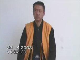 图片:原西藏拉萨哲蚌寺僧人洛桑旺秋接受当局的审讯。(视频截图)