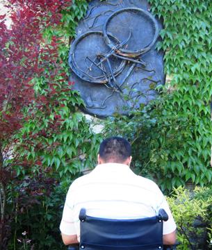 图片:轮椅上的方政,在多伦多大学校园内的六四纪念壁雕前,向受难者致敬(锡红摄)