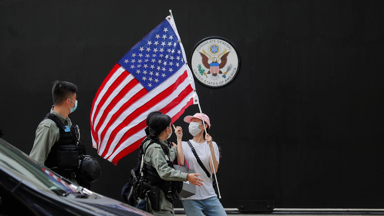 资料照:2020年7月4日,在美国驻港澳总领事馆外的一次抗议活动中,一名抗议者被香港防暴警察截查。(AP)