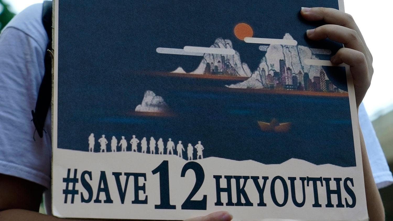 2020年12月28日,一名民主运动人士在中联办外举着标语牌,要求释放被中国当局扣留在海上的12名香港人。 (AP)
