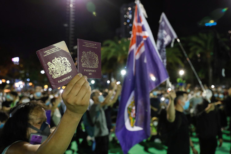 图为一名香港示威者举起英国国民海外护照(BNO)。(路透社图片)