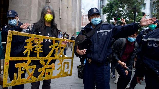 """2021年2月9日,民主运动人士在香港终审法院外抗议,手拿示威牌""""释放政治犯""""。(photo:RFA)"""