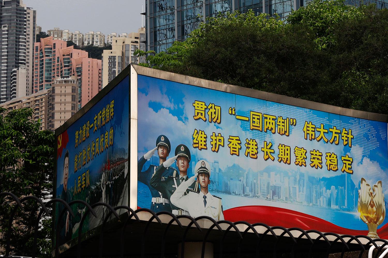 """学者认为,港版国安法在港人心目中等同宣告一国一制,新一轮的移民潮将迅速展开。图为,2020年5月22日,标有""""贯彻'一国两制'伟大方针 维护香港长期繁荣稳定""""的宣传牌,在中国人民解放军驻香港部队大厦展示。(美联社)"""