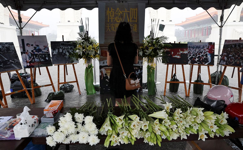 2021 年 6 月 4 日,臺灣台北自由廣場,一名婦女在紀念六四 32 週年的臨時紀念碑上表達敬意。(路透社)