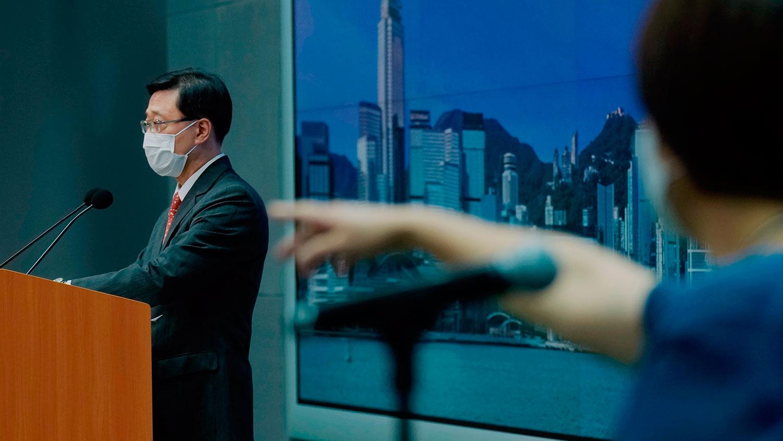 2021 年 6 月 17 日,香港保安局局长李家超(左)在新闻发布会上记者提问。 (美联社)