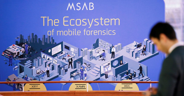 图为,2020年2月4日,在德国柏林举行年度欧洲警察大会上,一名男子站在MSAB广告(一家用于移动设备检查的取证技术的公司)的面前。(路透社)