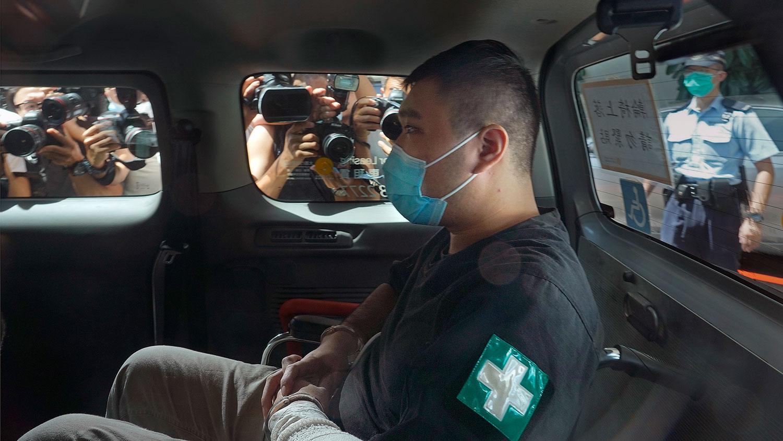 2020年7月6日,香港首位被控涉嫌违反国安法的男子唐英杰坐着轮椅由警车押解至法庭。(美联社)