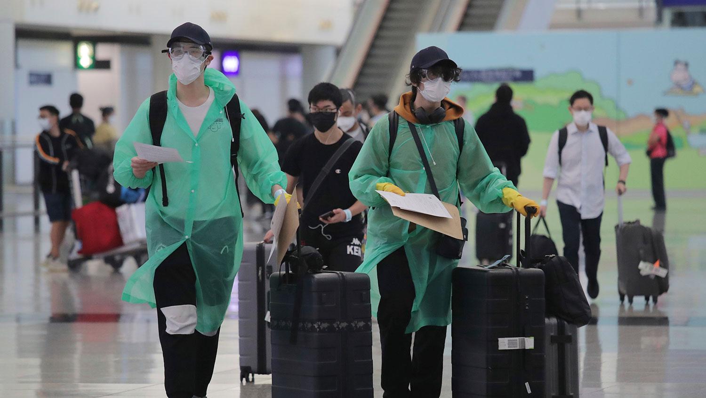 2020年3月23日,乘客在抵达香港机场,穿着防护服和口罩以保护自己免于感染冠状病毒。(美联社)