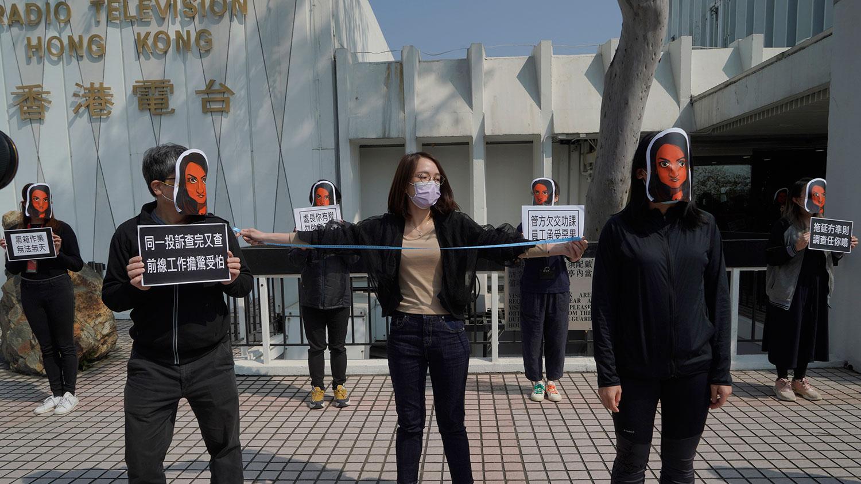 资料图片:2021年1月28日,香港公共广播电台(RTHK)员工戴着新闻工作者利君雅(Nabela Qose)的面具,管理层对利君雅的对待进行无声抗议。 利君雅现为香港电台助理节目主任及香港电台电视部节目《视点31》主持人。 (AP)