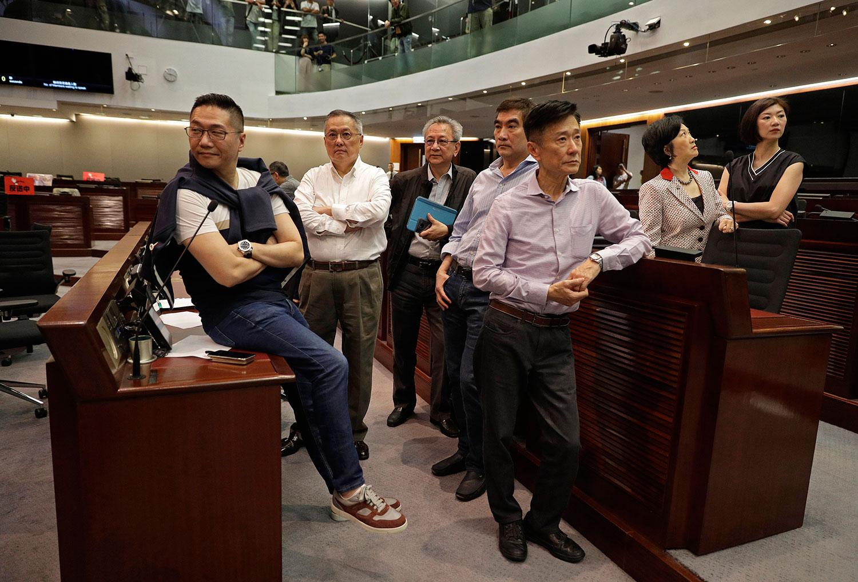 资料图片:2019年5月11日,香港民主建制两派议员就逃犯条例修订案在立法会发生冲突。图为亲北京的建制派议员在立法会上。(美联社)