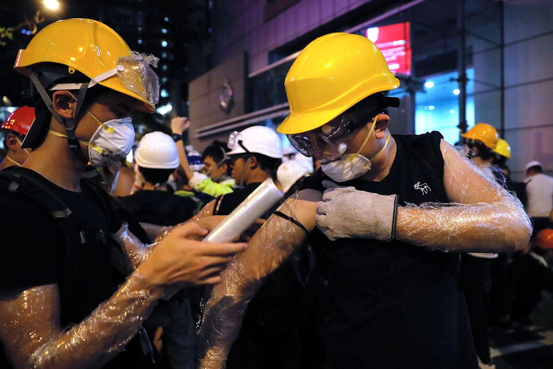 2019年6月21日,抗议者聚集在香港警察总部附近,用塑料包裹手臂以防胡椒喷雾。(美联社)