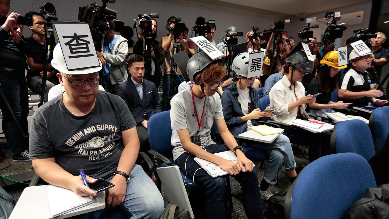 """2019年11月4日,多位香港记者在头戴""""查警暴止警谎""""标语的头盔等候警方举行记者会。(美联社)"""