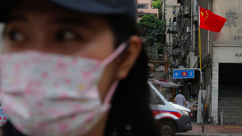 2021 年 7 月 1 日,在香港的一条街道上,一名妇女走过一辆停在中国国旗下的警车。 (美联社)