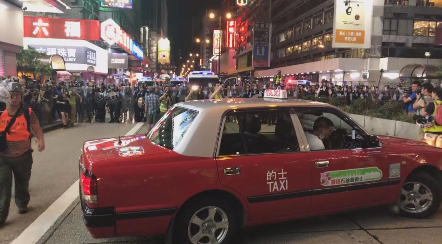 旺角清场期间,一名计程车司机把车横停在马路中间,阻止警方列队前行。(立场新闻视频截图)