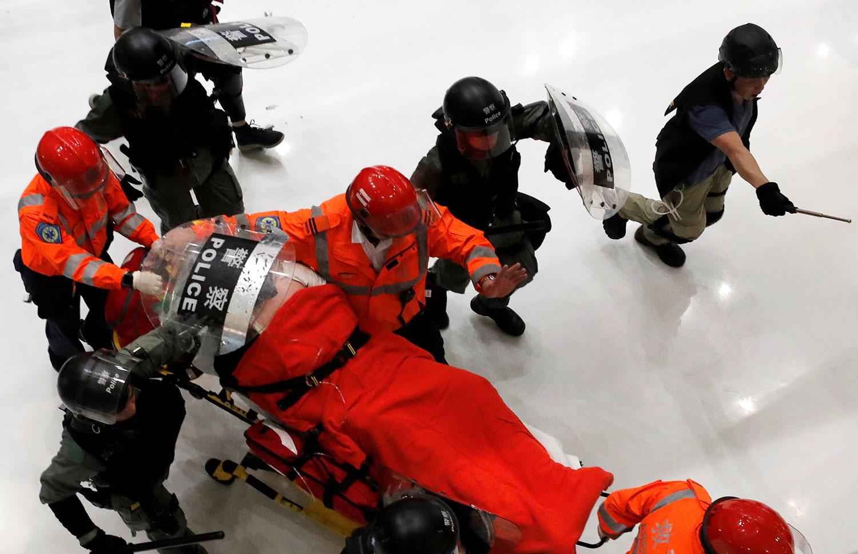 """2019年7月14日,沙田区的""""反送中""""大游行后,紧急救援人员在警方试图驱散抗议者后,将一名受伤的人员从商场撤离。(路透社)"""