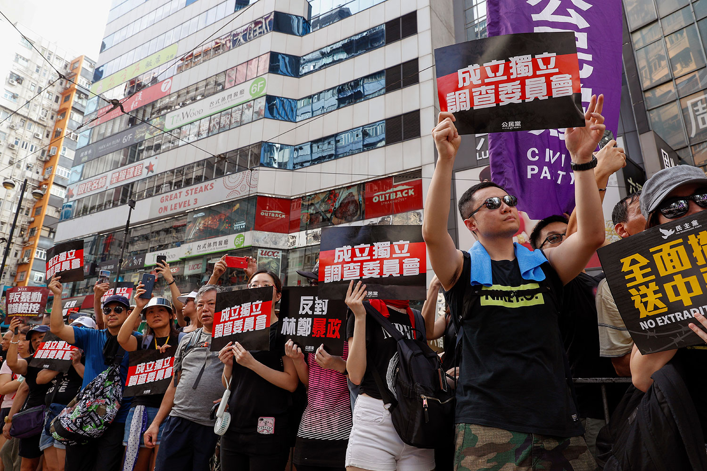 """资料图片:2019年7月21日,香港反送中大游行时,示威者举着标语""""成立独立调查委员会""""。(美联社)"""