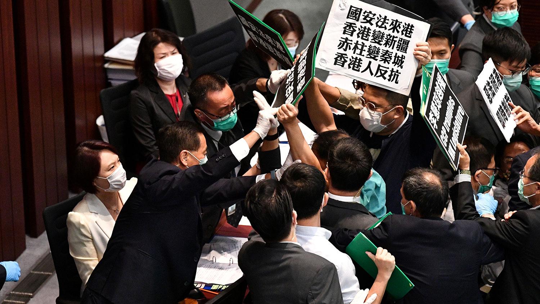 """资料图片:2020年5月22日,香港立法会泛民主派议员在内务委员会的一个会议期间举牌抗议北京强推""""港版国安法"""",他们被保安阻拦。(法新社)"""