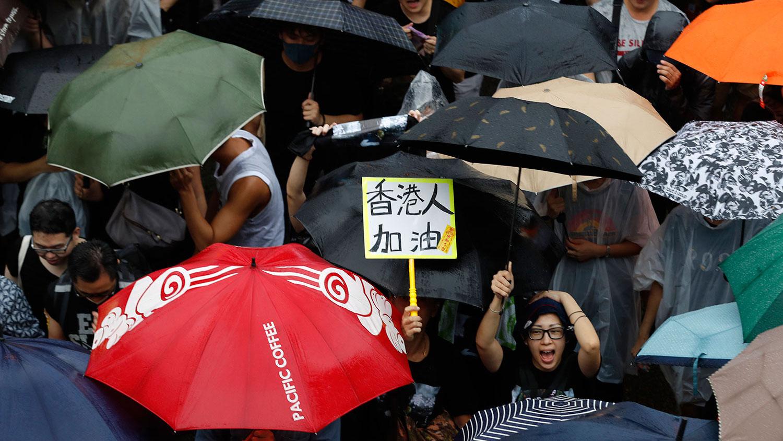 """资料图片:2019年8月18日,香港反送中大游行,市民手持标语牌:""""香港人 加油""""。(美联社)"""