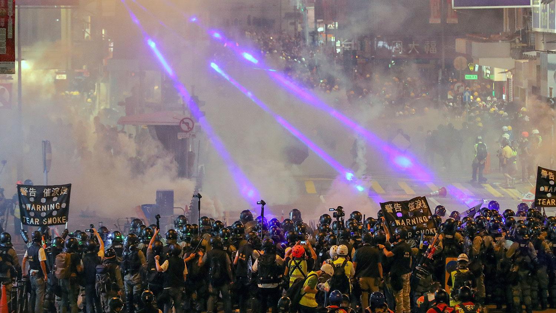 2019年8月4日,香港反送中期间,防暴警察向街道上的示威者发射催泪瓦斯。(美联社)