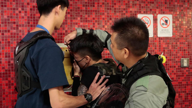2019年9月2日,香港地铁站封锁了火车门后,警察取下抗议者的面罩。(美联社)