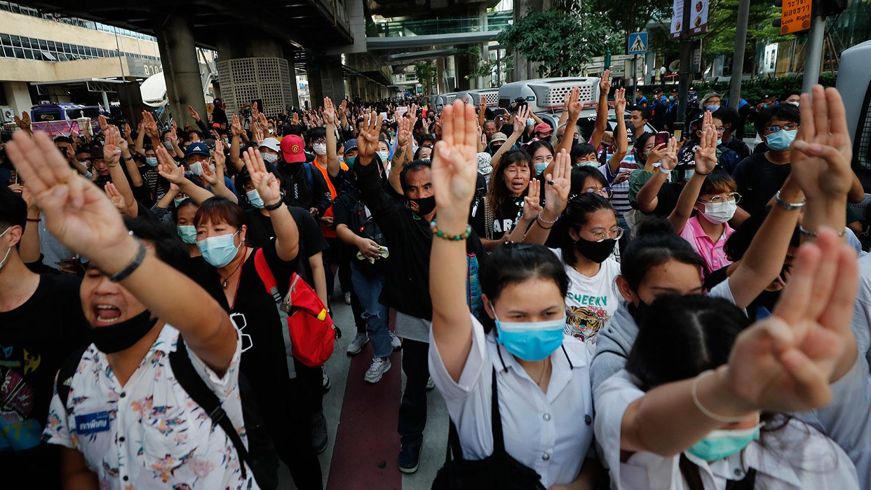 """2020年10月15日,示威者在曼谷举起代表""""和平、自由及弟兄姊妹情谊""""的""""三指"""",象征对当局的反抗。(AP)"""