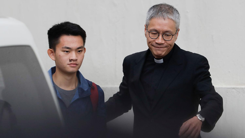 2019年10月23日,陈同佳(中)在媒体记者面前鞠躬道歉后,然后与管浩鸣牧师(右)一同乘车离开。(美联社)