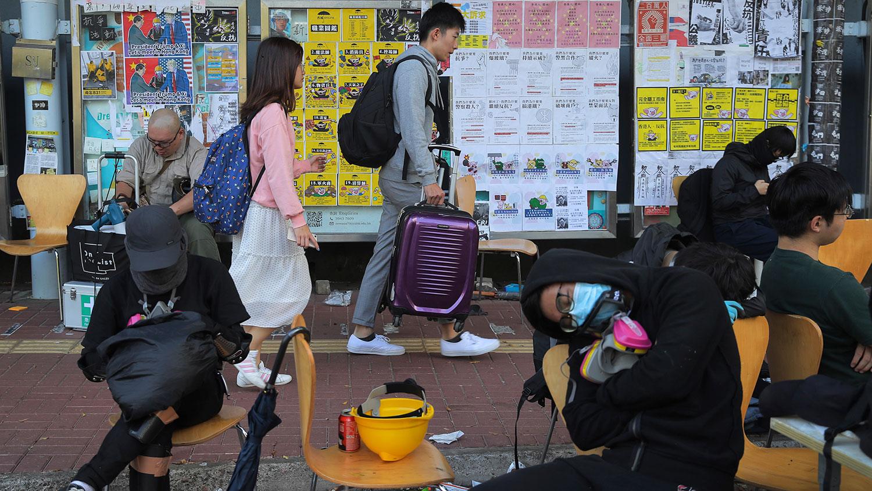 2019年11月13日,香港发生冲突后,学生拿着行李箱离开了香港中文大学。(美联社)