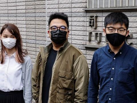 2020年11月23日,前香港众志秘书长黄之锋(右)、主席林朗彦(中)及成员周庭(左)抵达西九龙裁判法院出庭受审。(路透社)