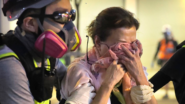 香港公立医院急症室黄医生指出近几个月的确多了吸入催泪弹后出现肚泻、月经失调、皮肤问题等个案。图为2019年11月2日,香港示威活动中,一名志愿医护人员送一名受催泪瓦斯影响的妇女。(资料图/美联社)