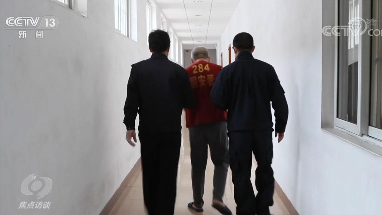 """中国央视新闻客户端《焦点访谈》""""起底""""双面人""""李亨利""""节目画面。(视频截图)"""