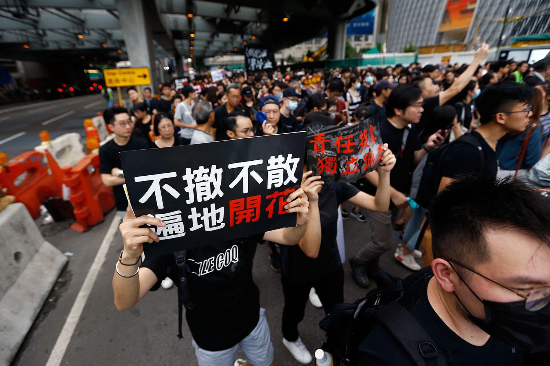 """2019年7月7日,香港反送中大游行,示威者手持标语牌""""不撤不散  遍地开花""""。(美联社)"""