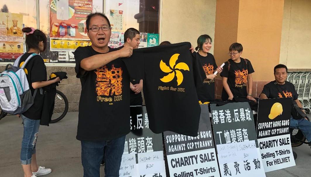全球支港联负责人赵昕卖T恤为港人换头盔(CK摄)