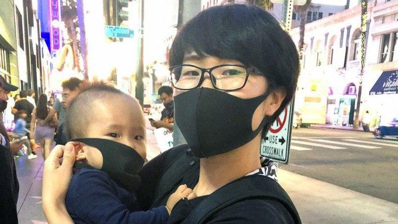 曾向五星紅旗潑墨的洛杉磯女青年楊曉爲自己和兒子帶上口罩蒙面撐香港(鄭存柱提供)