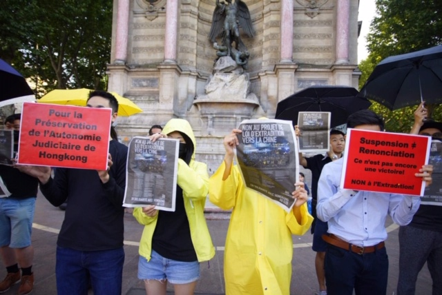 """法国的香港侨民以戏剧表演方式高举标语指出""""暂缓""""并不等于""""撤回""""。(蔡凌摄影)"""