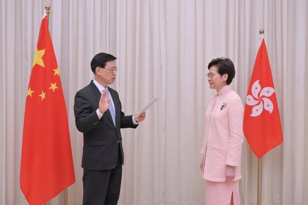 李家超(左)是从警察部门基层出身,又在加入政府前没有大学学历的政务司司长。
