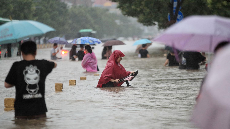 2021 年 7 月 20 日,河南省郑州市,居民在趟过洪水的街道上。(路透社)