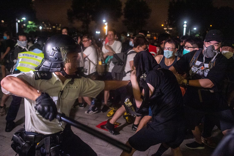2019年6月10日凌晨12点,一批戴上口罩和面罩的示威者手挽手闯进香港立法会示威区,推倒铁马,推向警察防线。抗议者与警察发生冲突。(法新社)