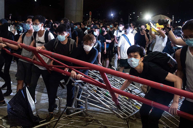 2019年6月10日凌晨12点,一批戴上口罩和面罩的示威者手挽手闯进香港立法会示威区,推倒铁马,推向警察防线。(法新社)