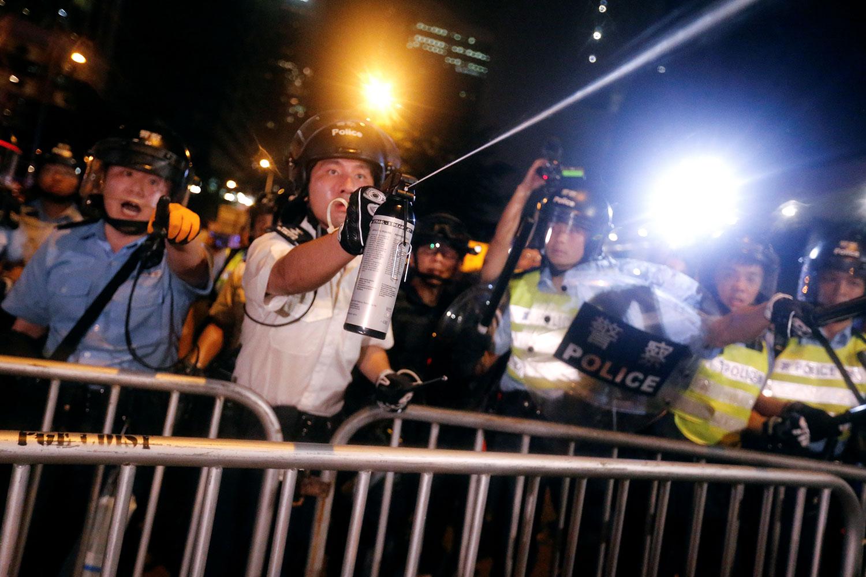 2019年6月10日凌晨12点,一批戴上口罩和面罩的示威者手挽手闯进香港立法会示威区,推倒铁马,推向警察防线。警员向多名示威者面部施放胡椒喷剂。(路透社)