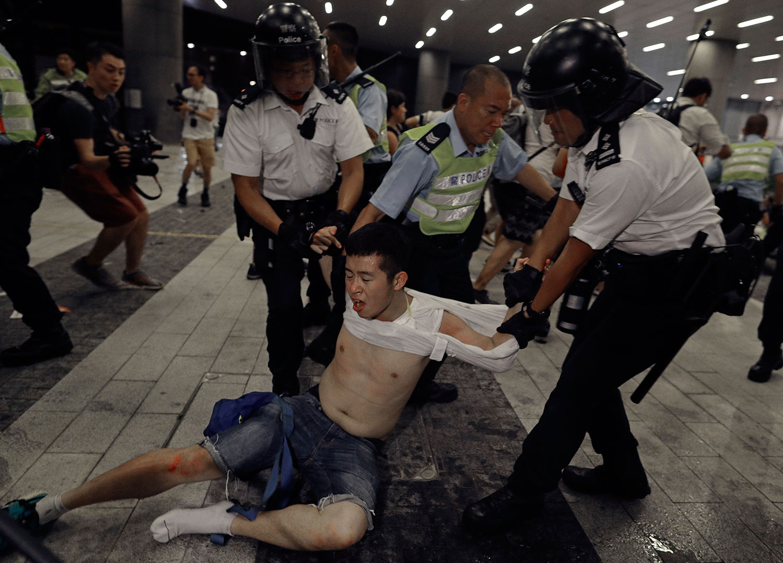 2019年6月10日凌晨12点,一批戴上口罩和面罩的示威者手挽手闯进香港立法会示威区,推倒铁马,推向警察防线。抗议者与警察发生冲突。(美联社)