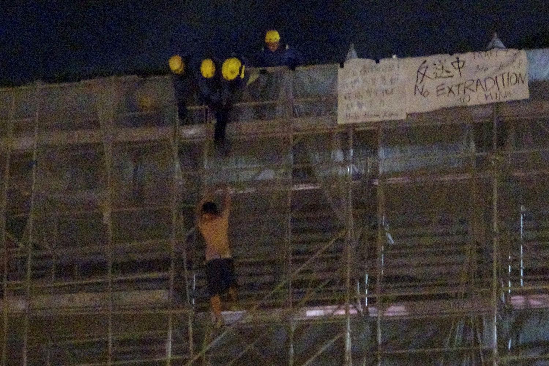 2019年6月15日,一名抗议者在太古广场平台悬挂标语时,从大楼周围的施工脚手架上掉下来,消防队员正试图营救他。(路透社)