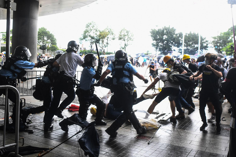 2019年6月12日,香港市民反《逃犯条例》示威活动中,多名防暴警察挥舞警棍殴打一名示威男子。(法新社)
