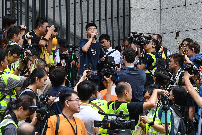 2019年6月21日,香港众志秘书长黄之锋(Joshua Wong)在警察总部外抗议时发表讲话,要求警务处处长卢伟聪撤回暴动定性,释放被捕人士。(法新社)
