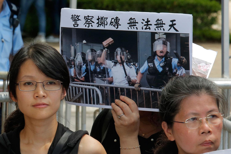 """2019年6月20日,来自示威学生的父母们和宗教的各种活动团体在警察总部外抗议,示威群众举着标语牌""""警察投掷砖 无法无天""""。(美联社)"""