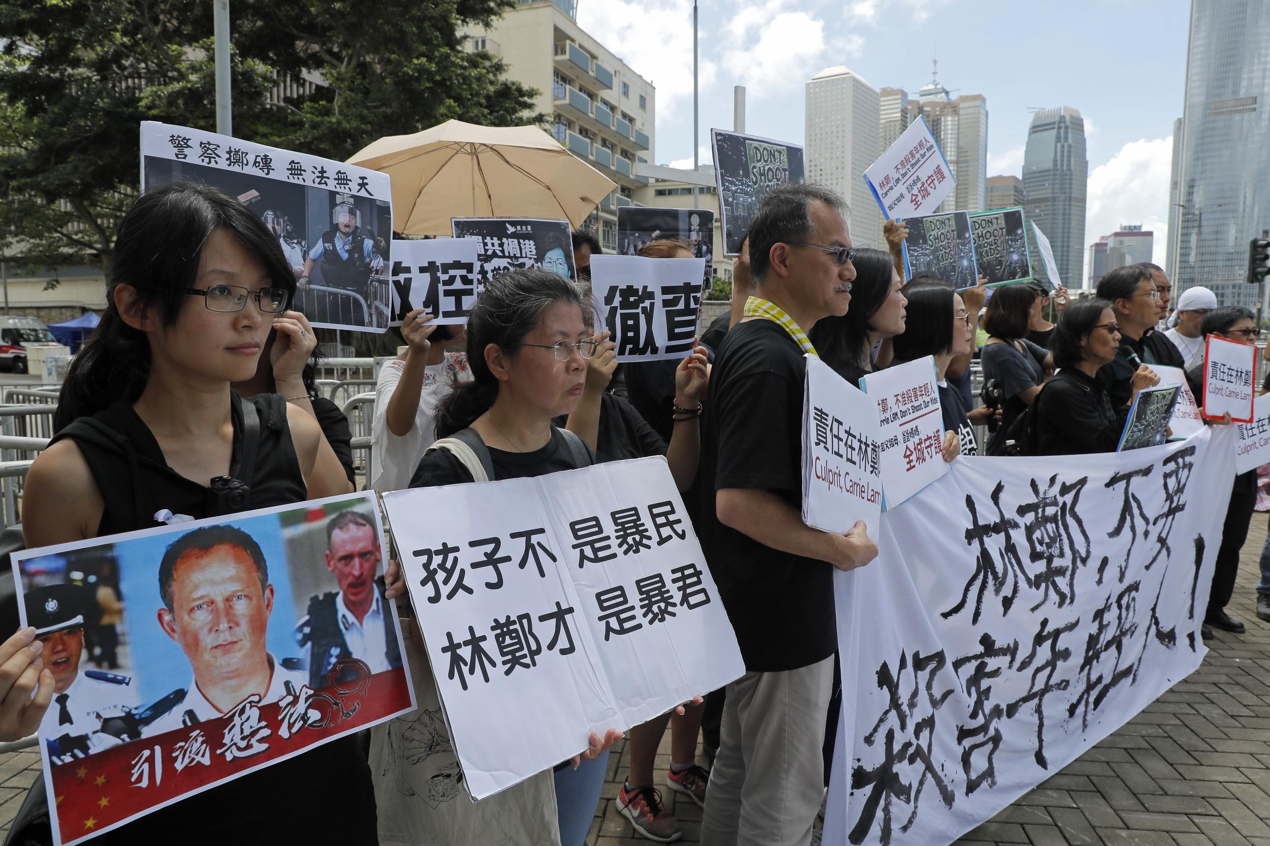 """2019年6月20日,香港示威学生的父母们和宗教的各种活动团体在在警察总部外抗议,示威者举着""""林郑不要杀害年轻人!""""等标语。(美联社)"""