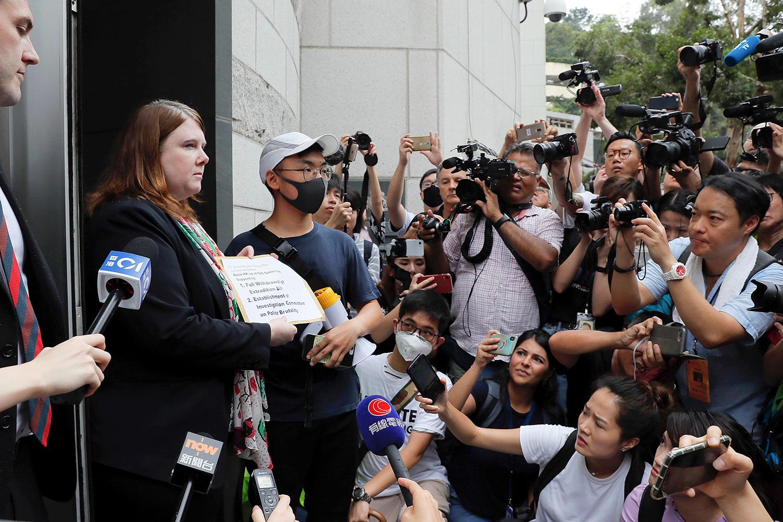 2019年6月26日,香港一批反对修订《逃犯条例》的市民响应网上号召,游行到多个成员国在香港的总领事馆请愿,要求关注香港状况。图为市民致函英国领事馆的一名代表。(美联社)