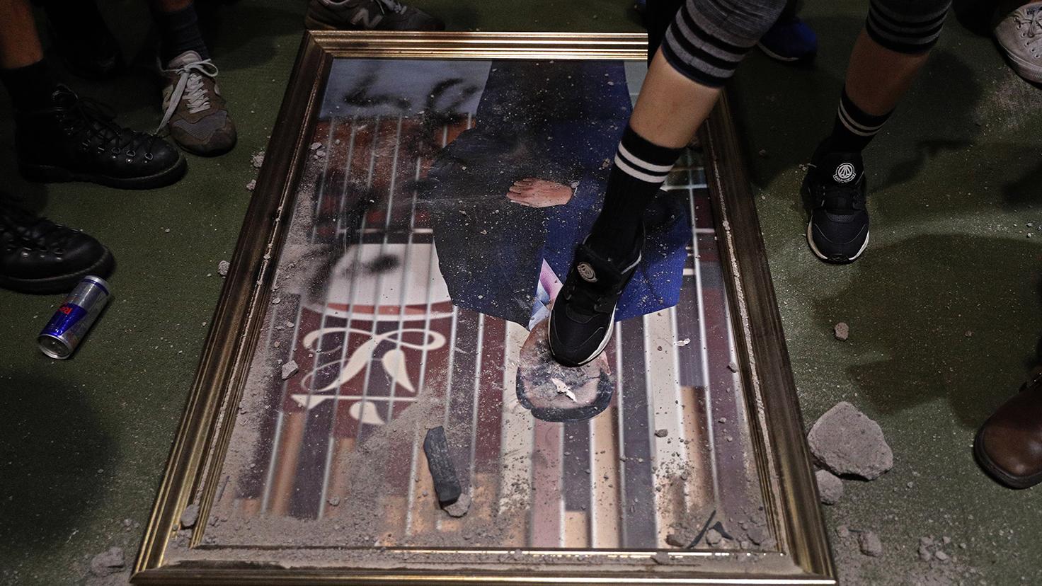 香港反对《逃犯条例》修订示威人士冲进香港立法会大楼拆下立法会领袖画像踩踏。(美联社)