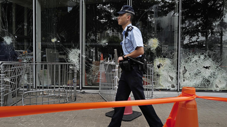 一名香港警察走过被破坏的立法会大楼外面。(美联社)